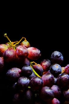 Close vertical de uvas vermelhas sob as luzes isoladas em um fundo preto