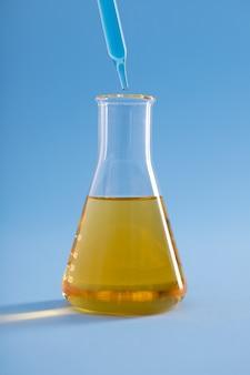 Close vertical do conta-gotas com líquido azul sobre o líquido amarelo do frasco erlenmeyer na superfície azul