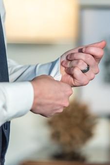 Close vertical do noivo usando sua aliança de casamento e fixando as abotoaduras