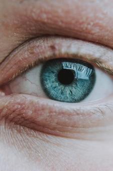 Close vertical do olho azul-claro de um humano idoso