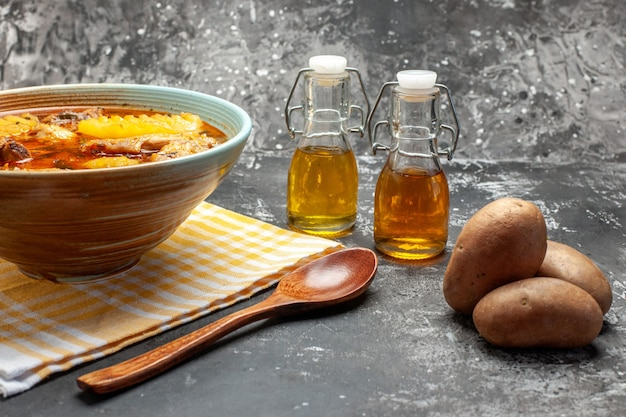 Closeu-up e vista lateral de deliciosa sopa com frango e batata e colher na mesa escura e cinza