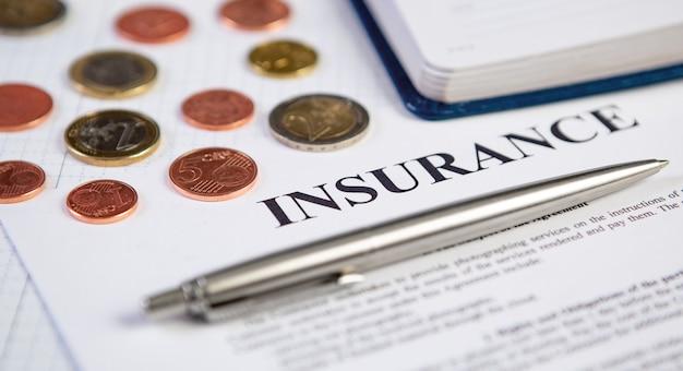 Closeup a caneta prata moderna no contrato de seguro com moedas e planejamento em segundo plano.