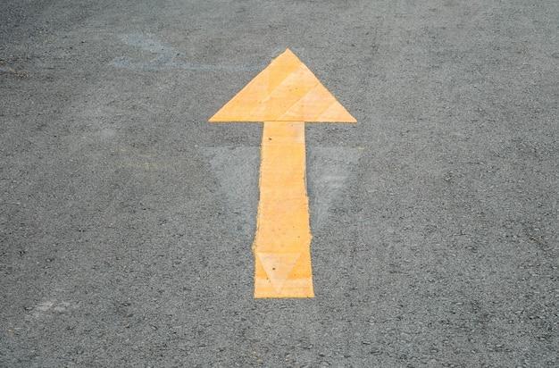 Closeup amarelo pintado sinal de seta no fundo do chão de rua de cimento
