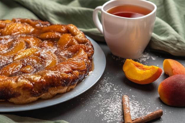 Closeup arte tatina com caramelo de pêssegos e açúcar de confeiteiro em um prato branco sobre um fundo escuro