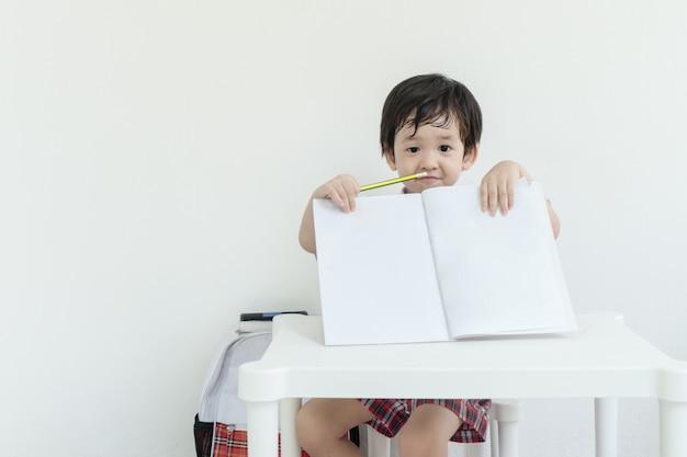 Closeup asain kid mostrar um caderno após a escola na parede de cimento branco