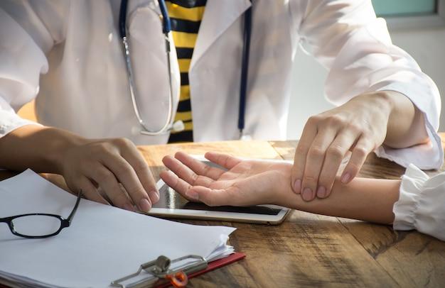 Closeup asiático médico está verificando o pulso da paciência pelos dedos