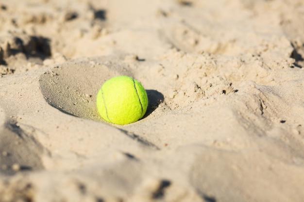 Closeup atirou uma bola de tênis na areia. espaço vazio