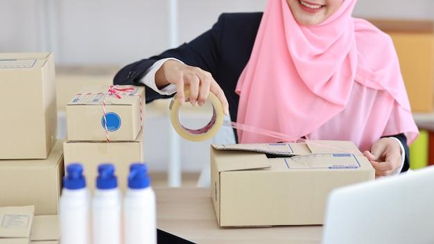 Closeup ativa muçulmana asiática com as mãos em terno azul, sentado e trabalhando na entrega da caixa do pacote online. pequena empresa iniciante pme freelance trabalhando no computador e no celular com uma cara feliz