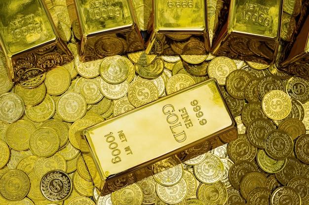 Closeup barra de ouro brilhante de 1 kg no lote da pilha de moedas de ouro