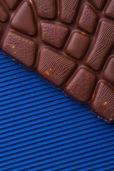 Closeup barra marrom de chocolate ao leite sobre fundo azul