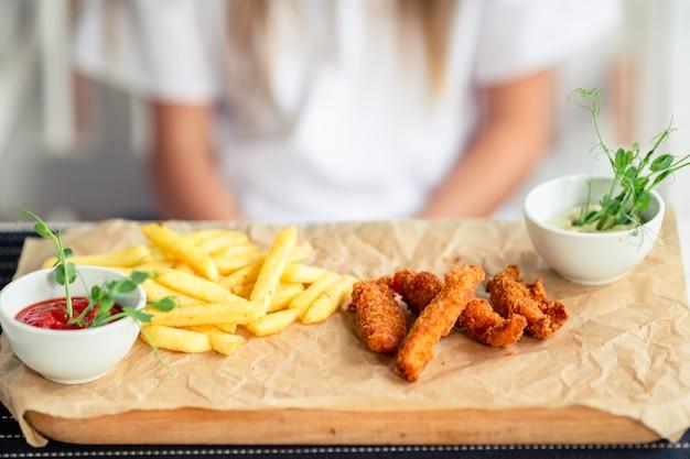 Closeup batata frita crocante com dois molho e os dedos de frango fresco, servidos na placa de madeira rústica