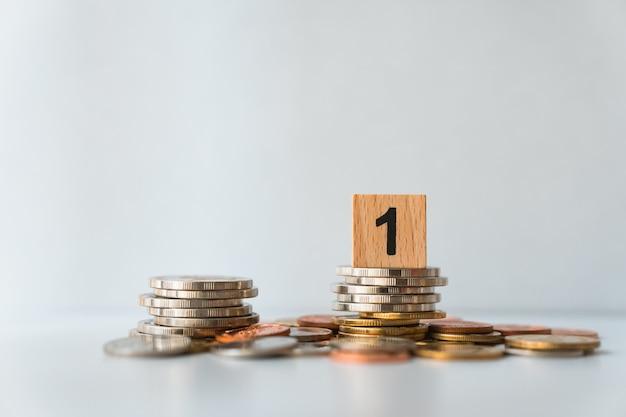 Closeup bloco de madeira número um em moedas de pilha usando como conceito de negócios e finanças