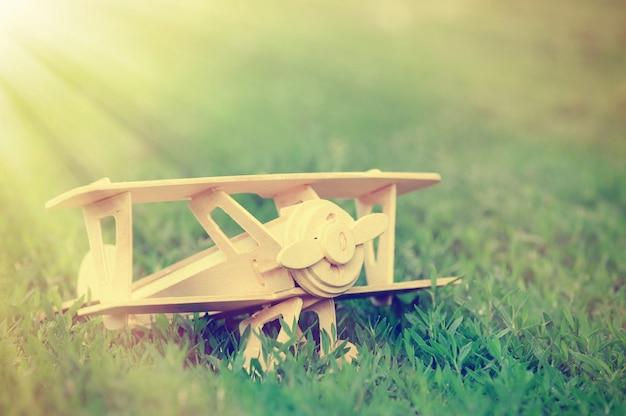 Closeup brinquedo de avião de madeira no fundo do chão de grama