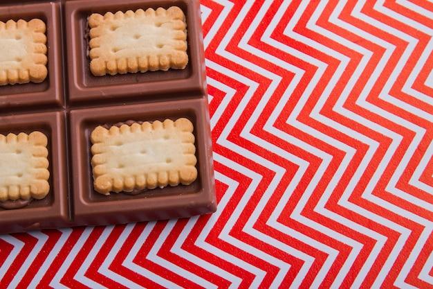 Closeup canto da barra de chocolate em fundo vermelho e branco ondulado