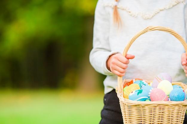 Closeup cesta cheia de ovos de páscoa coloridos nas mãos de crianças