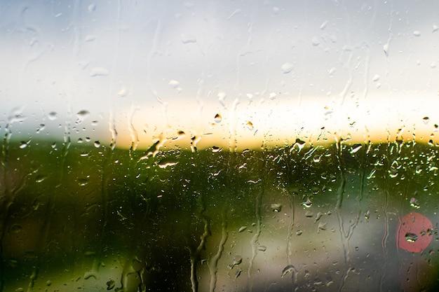 Closeup chuva cai na superfície da janela brilhante