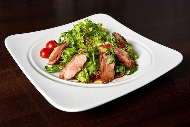 Closeup com fome de um bife grelhado fatiado servido com salada de folhas verdes e tomate cereja em um prato quadrado branco em cima da mesa no restaurante.