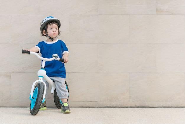 Closeup criança asiática andar de bicicleta e olhar para o espaço da imagem