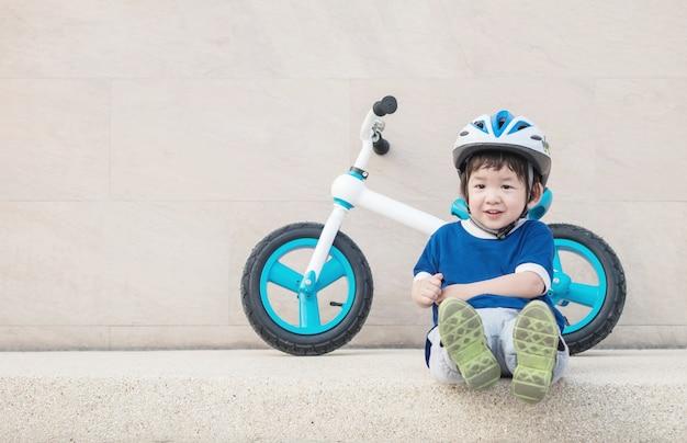 Closeup criança feliz com cara de sorriso sente-se no chão de pedra de mármore com bicicleta