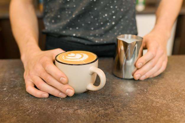 Closeup da arte do café com leite, mãos do barista e caneca de ferro com leite