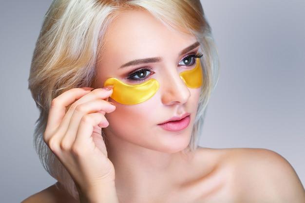 Closeup da bela mulher sorridente feliz com hidratante sob máscara de olho
