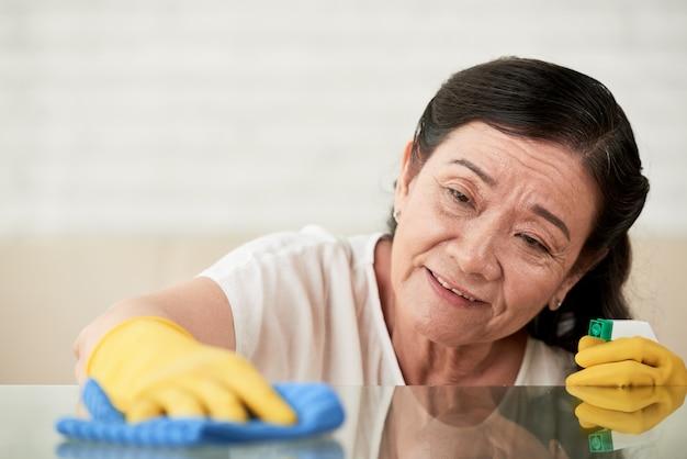 Closeup da empregada doméstica polir mesa de vidro com limpador de spray de vidro