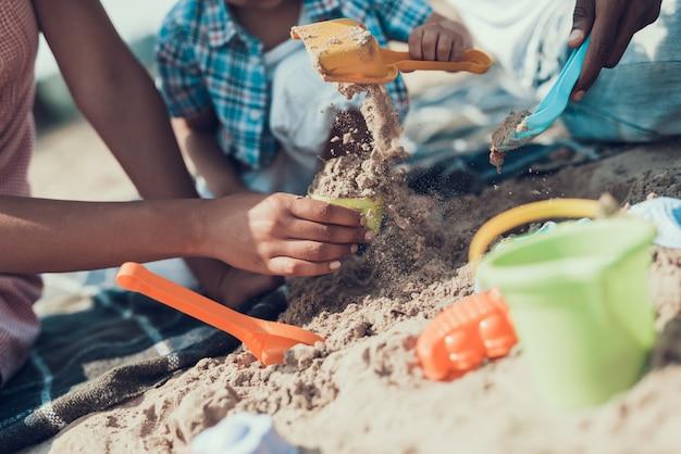 Closeup da família é brincar com brinquedos na praia de areia do rio