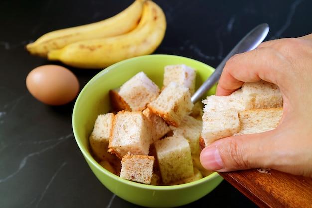 Closeup da mão adicionando pão multigrãos em cubos à mistura para assar pudim de pão de banana