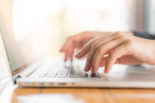 Closeup da mão da mulher de negócio que datilografa no teclado do portátil.