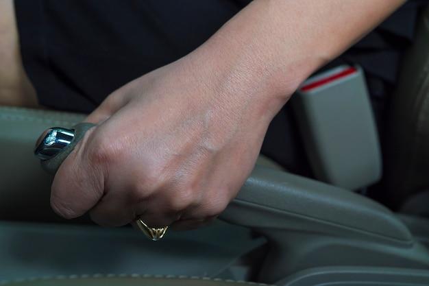 Closeup da mão da senhora puxa o freio de mão do carro