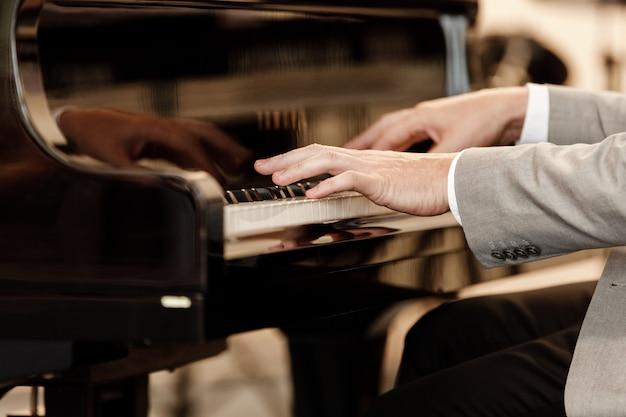 Closeup da mão de um músico tocando piano