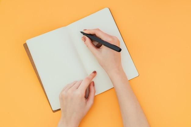 Closeup da mão de uma mulher com uma caneta, escreve em um caderno limpo em uma superfície laranja