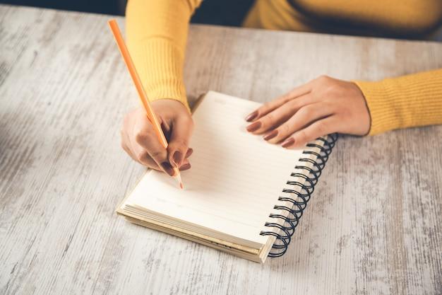 Closeup da mão de uma mulher escrevendo no papel