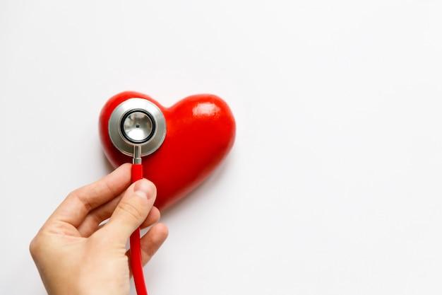 Closeup da mão do homem segurando um estetoscópio vermelho no coração - dispositivo de diagnóstico médico para ausculta (escuta) de sons provenientes do coração