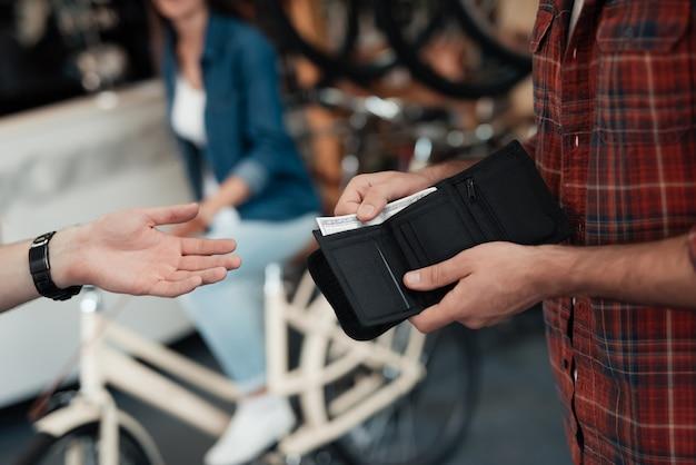 Closeup da mão masculina dá dinheiro ao vendedor