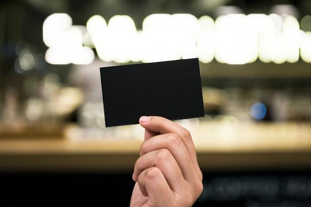 Closeup da mão segurando o cartão de papel preto