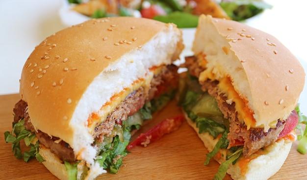 Closeup da textura do hambúrguer cortado servido na tábua de pão de madeira