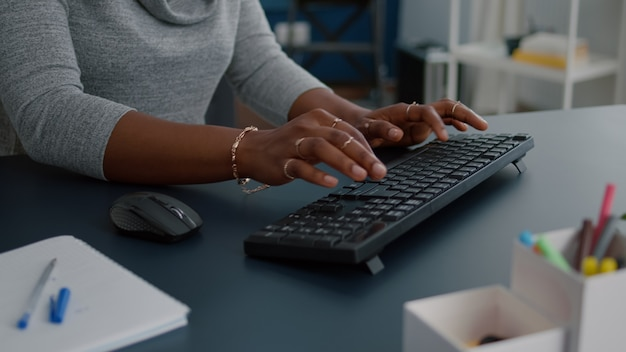 Closeup das mãos do aluno trabalhando no projeto de comunicação, digitando informações no teclado usando o computador sentado na mesa na sala de estar