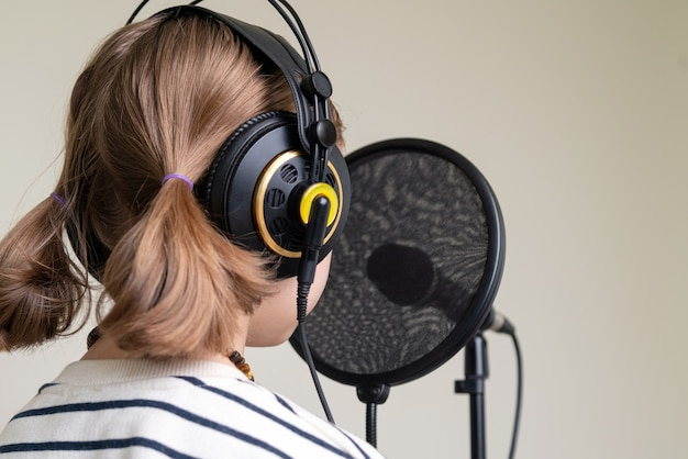 Closeup de adolescente gravando música em estúdio em casa.