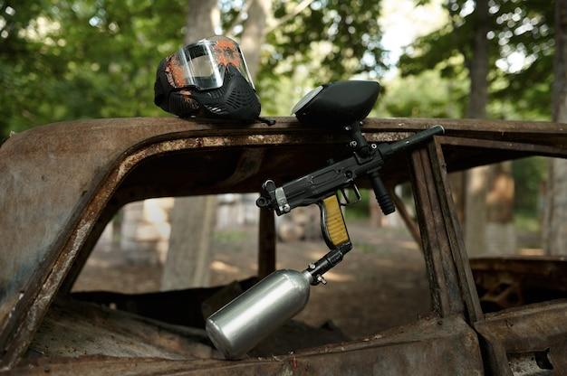 Closeup de arma de paintball e máscara de proteção, ninguém, playground na floresta no fundo. esporte extremo ao ar livre, arma pneumática e balas de tinta, conceito de jogo de equipe militar