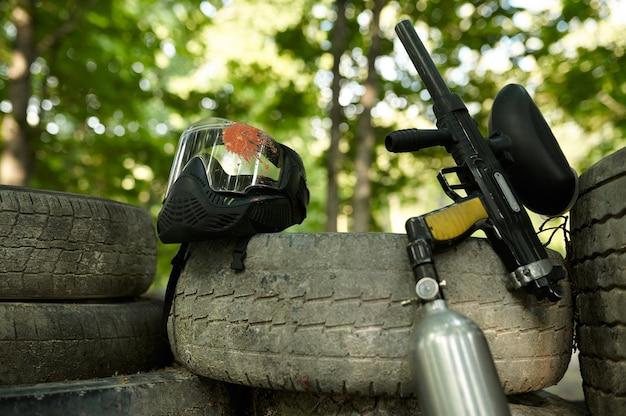 Closeup de arma de paintball e máscara de proteção, ninguém, playground na floresta no fundo. esporte extremo ao ar livre, arma pneumática e balas de tinta, conceito de jogo militar