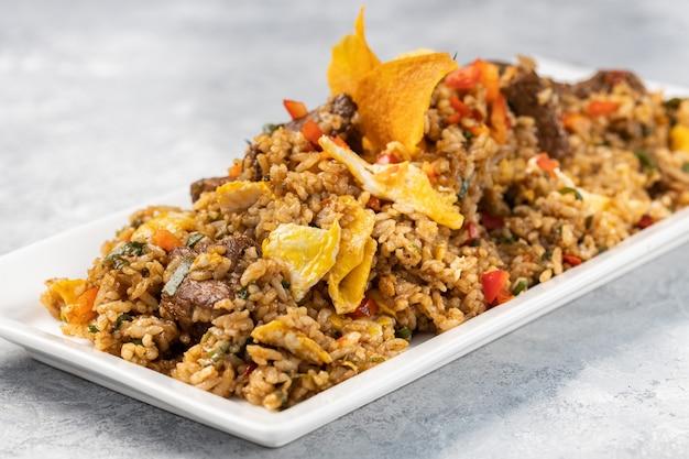 Closeup de arroz cozido picante com carne, vegetais e batatas fritas em um prato sobre a mesa