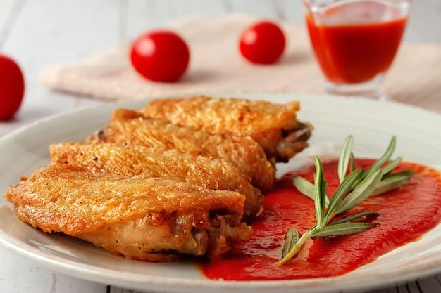 Closeup de asas de búfalo cozidas na hora com molho de tomate e tomates