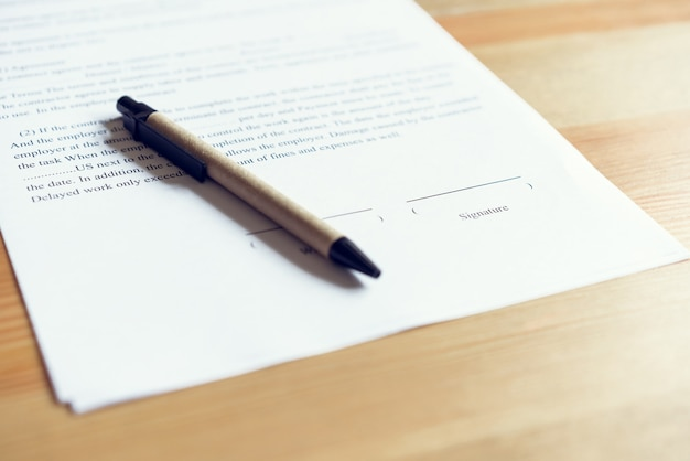 Closeup de assinar um acordo de documentação e caneta na mesa.