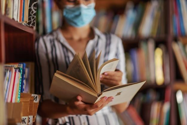 Closeup de atraente universitária em pé na biblioteca com máscara facial e lendo um livro. estudando durante o conceito de vírus corona.