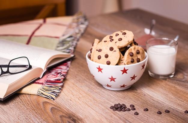 Closeup de biscoitos de chocolate em uma tigela de estrelas e um copo de leite sobre um fundo de madeira