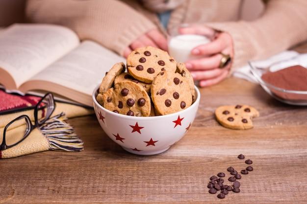 Closeup de biscoitos de chocolate em uma tigela de estrelas sobre uma mesa com mãos femininas segurando um copo de bebida quente no fundo