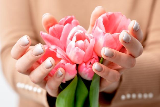 Closeup de botões de tulipa rosa nas mãos de uma jovem. flores cor de rosa em mãos femininas