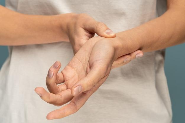 Closeup de braços de mulher segurando seu pulso dolorido. síndrome do túnel do carpo, artrite, conceito de doença neurológica