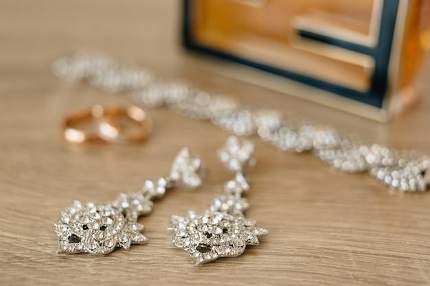 Closeup de brincos com anéis de casamento de ouro e pulseira na cena desfocada
